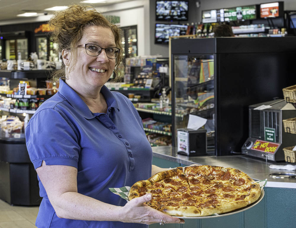 woman smiling and holding pizza